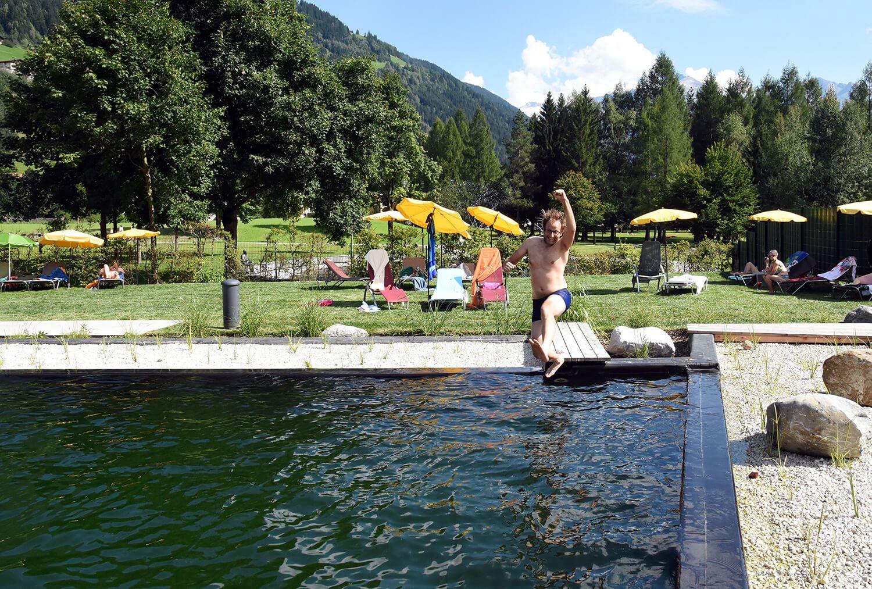 Sprung in den Thermalwasser Badesee der Alpentherme Gastein