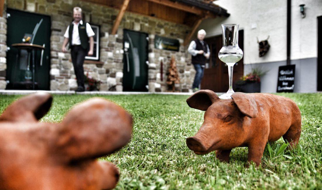 Auf einem kleinen Holzschwein wird auf der Wiese vor der Schnapsbrennerei ein Schnapsglas balanciert.