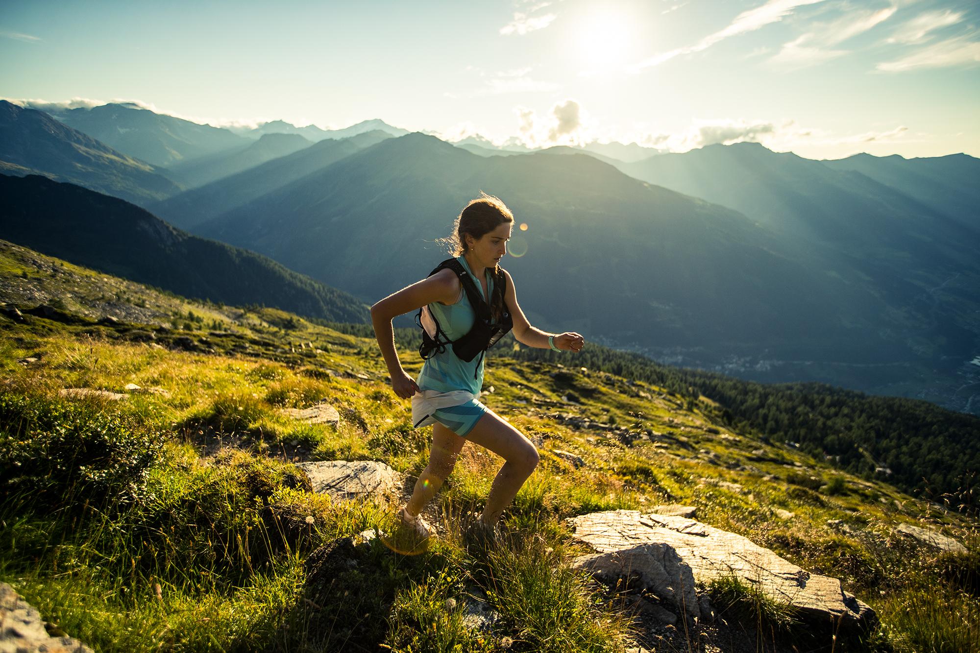 Bergläuferin vor den Bergen Gasteins im Sonnenuntergang