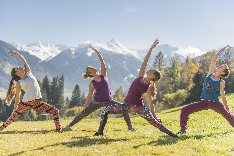 4 Frauen betreiben Yoga auf einer Wiese