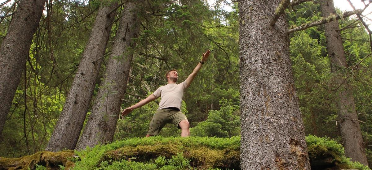 Mann im Wald in der Pose des friedvollen Kriegers