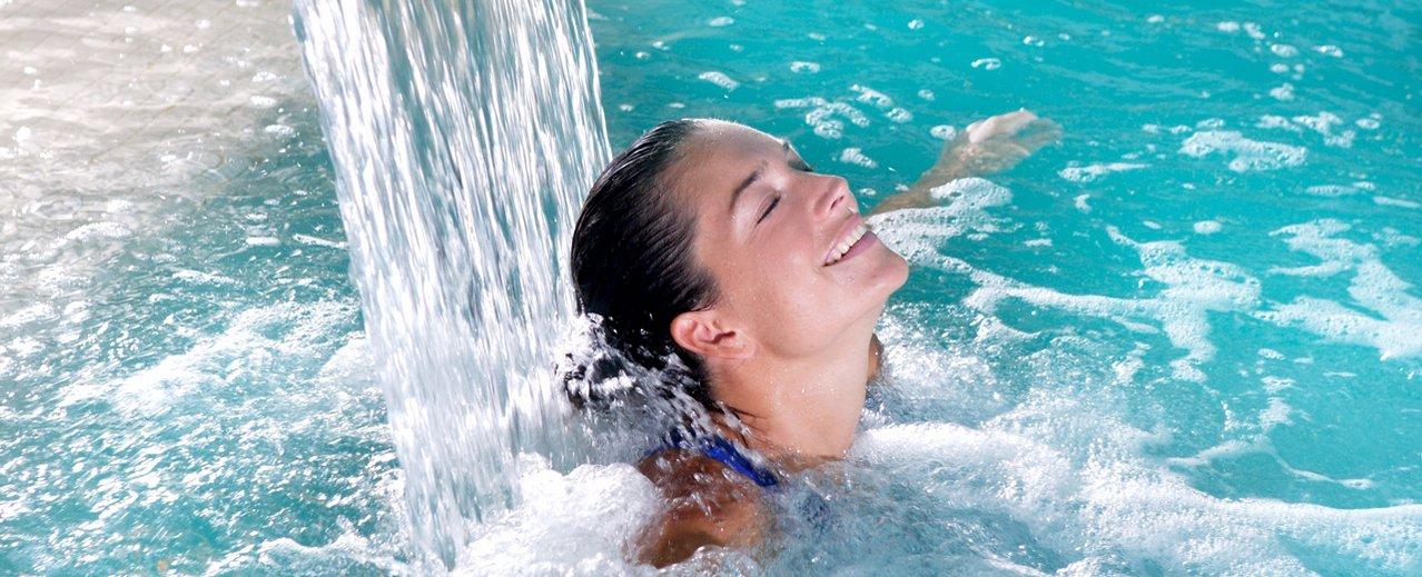 Dame im Thermalwasserbecken unter einem kleinen Wasserfall