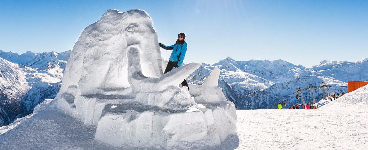 Schneeskulptur Mammut mit Schifahrerin im Vordergrund, Hintergrund blauer Himmel und Berge