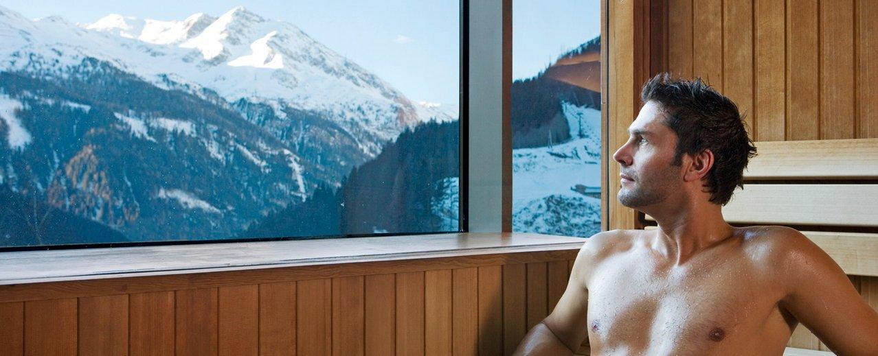 Mann in der Panoramasauna mit Blick auf die Bergwelt Gasteins