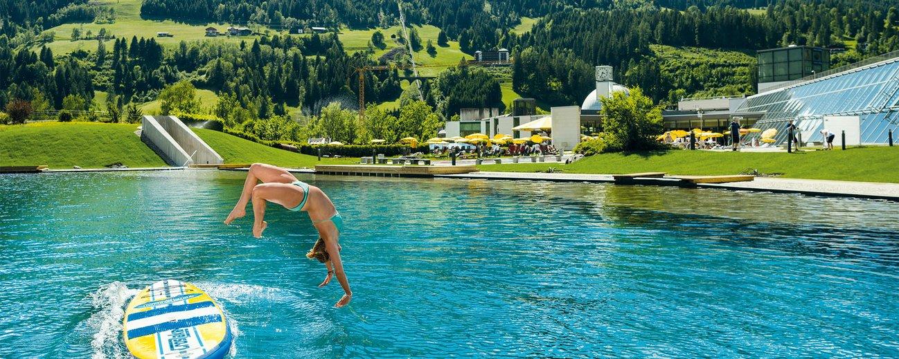 Frau taucht ins Außenbecken der Alpentherme Bad Hofgastein ein