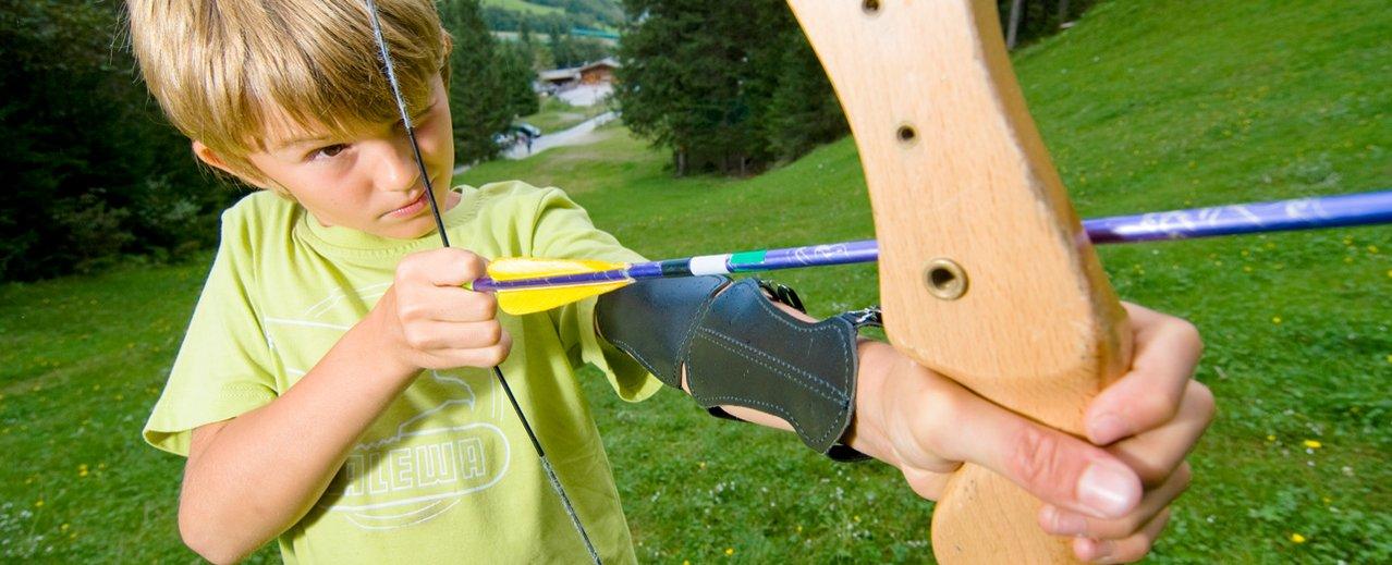 Ein Kind legt den ersten Pfeil in den Bogen. Bogenschießen in Gastein