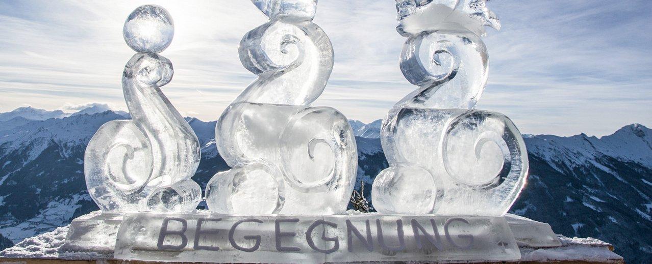 Eisskulptur am Berg mit Bergpanorama im Hintergrund